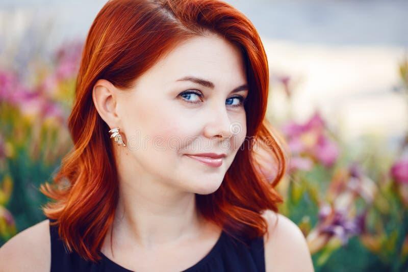 O retrato do close up do meio envelheceu a mulher caucasiano branca com cabelo vermelho encaracolado acenado no vestido preto que imagens de stock royalty free