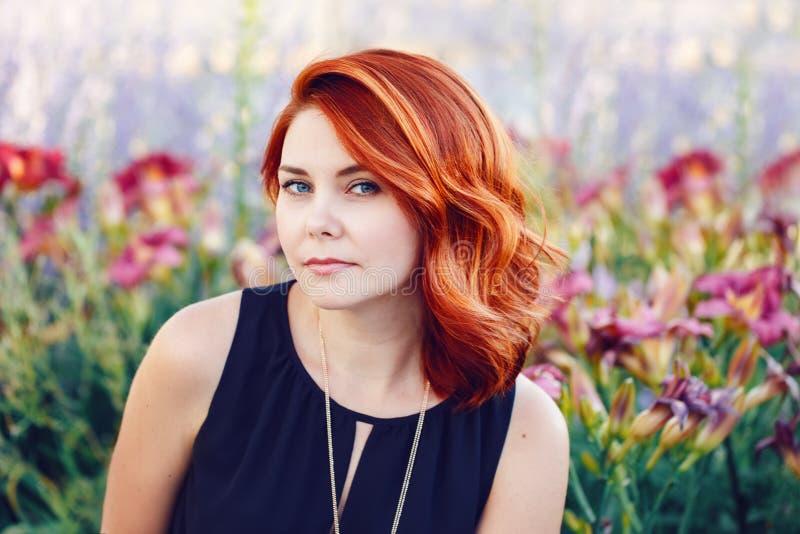 O retrato do close up do meio envelheceu a mulher caucasiano branca com cabelo vermelho encaracolado acenado no vestido preto que fotografia de stock royalty free
