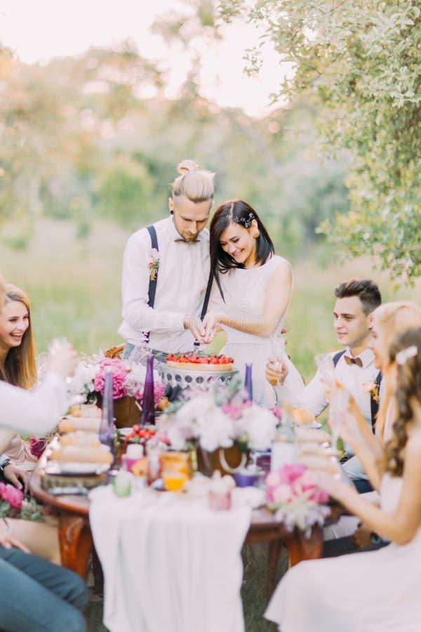 O retrato do close-up dos convidados do casamento e do justo casado cortando sua parte do fisrt do bolo de casamento junto imagem de stock royalty free