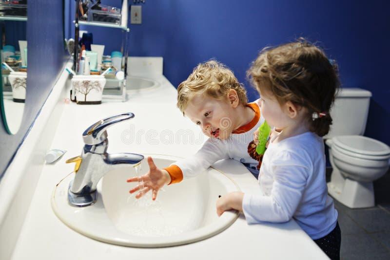 O retrato do close up dos gêmeos caçoa a menina do menino da criança nas mãos de lavagem da cara do toalete do banheiro que escov fotografia de stock royalty free