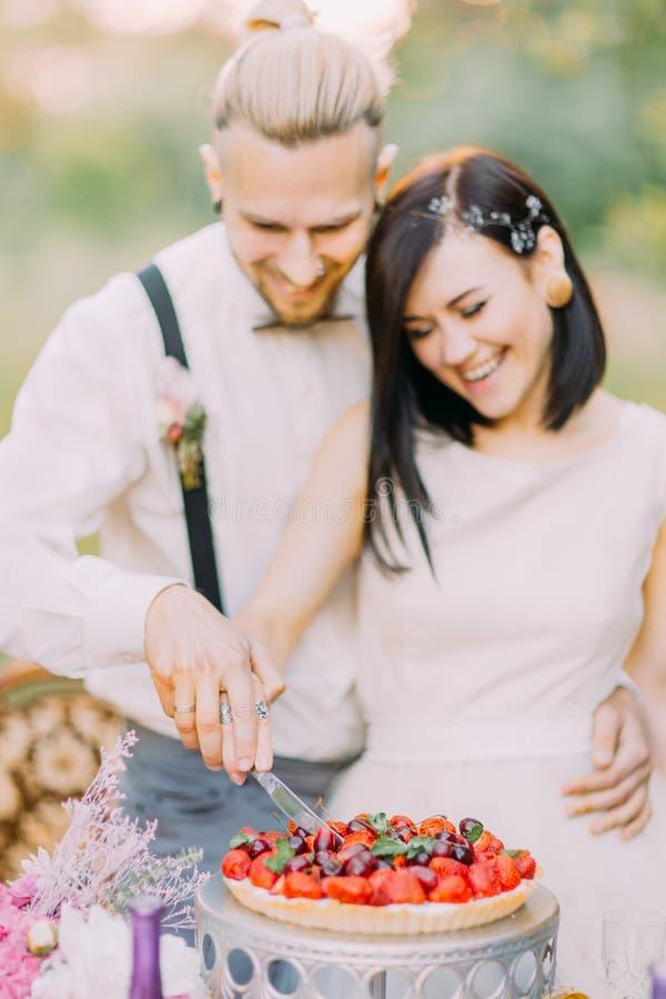 O retrato do close-up dos pares borrados do recém-casado que cortam o bolo de casamento com cerejas e morangos E imagens de stock royalty free