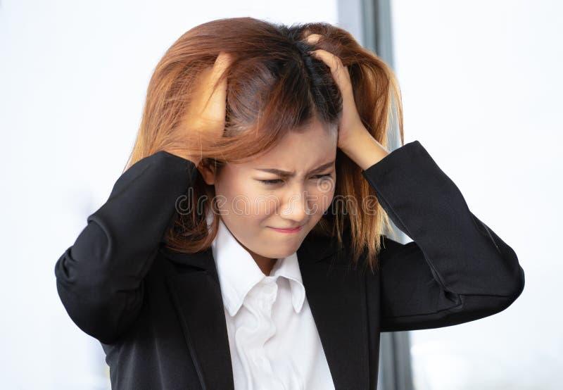 O retrato do close up forçou, mulher de negócios asiática nova forçou está indo louco puxando seu cabelo na frustração no escritó fotos de stock royalty free