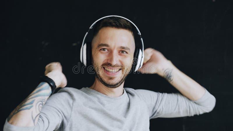 O retrato do close up do homem engraçado novo põe sobre fones de ouvido e a dança louca quando escute a música no fundo preto fotografia de stock