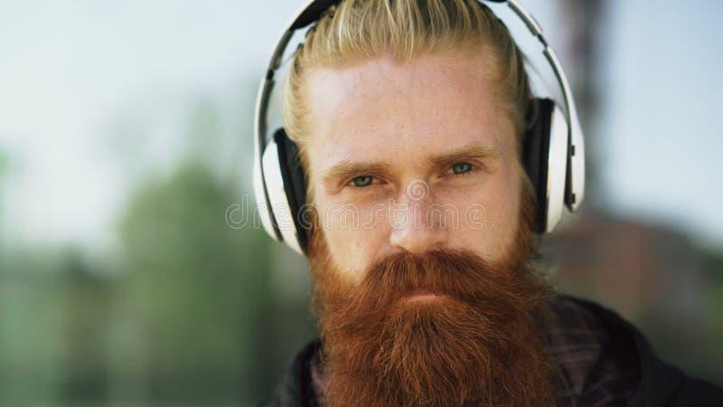 O retrato do close up do homem farpado novo do moderno com fones de ouvido escuta a música e o sorriso na rua da cidade imagem de stock