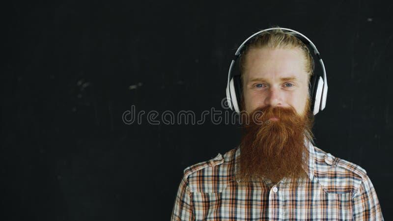 O retrato do close up do homem novo farpado nos fones de ouvido escuta a música e a vista no sorriso da câmera fotografia de stock royalty free