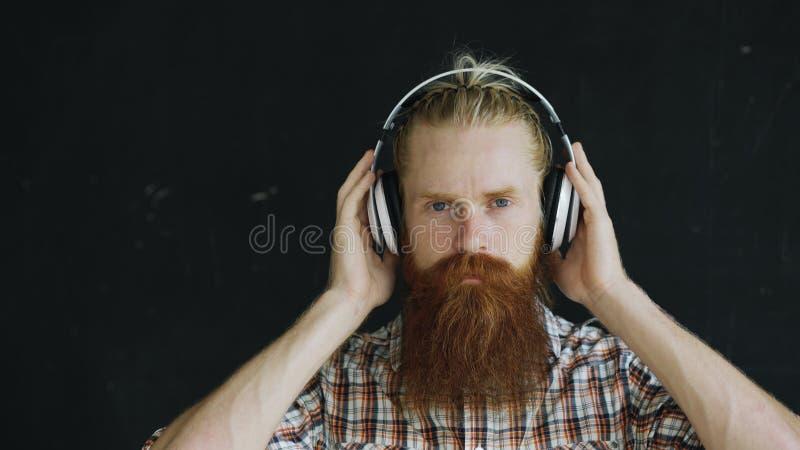 O retrato do close up do homem novo farpado nos fones de ouvido escuta a música e a vista no sorriso da câmera imagens de stock royalty free