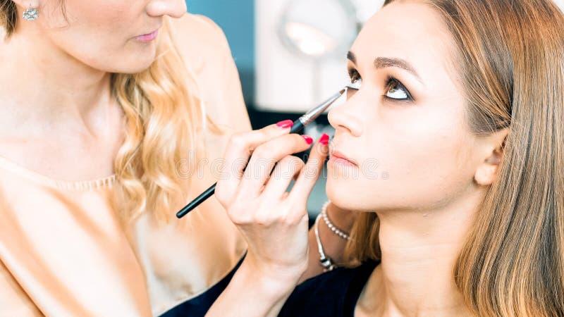 O retrato do close up do ` profissional s do modelo da pintura do maquilhador eyes imagem de stock