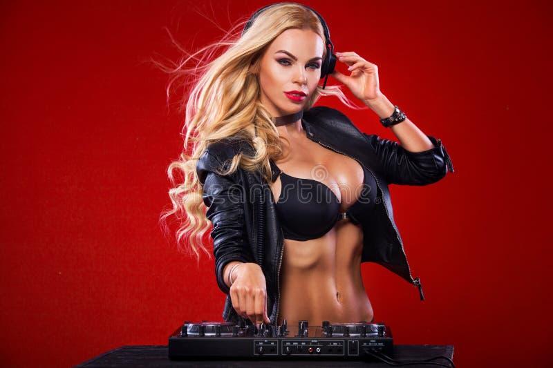 O retrato do DJ 'sexy' com a plataforma de registro que joga a música e escuta som no fundo vermelho foto de stock royalty free