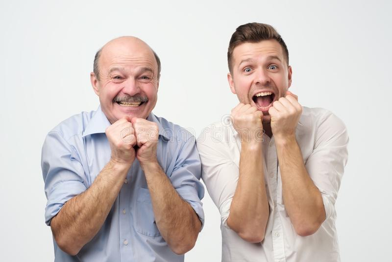 O retrato do dois homens surpreendidos gena e filho ou melhores amigos que olham a câmera com a boca aberta foto de stock royalty free