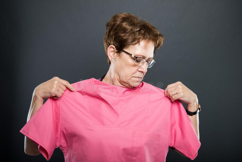 O retrato do doutor superior da senhora que tenta sobre esfrega a camisa foto de stock royalty free
