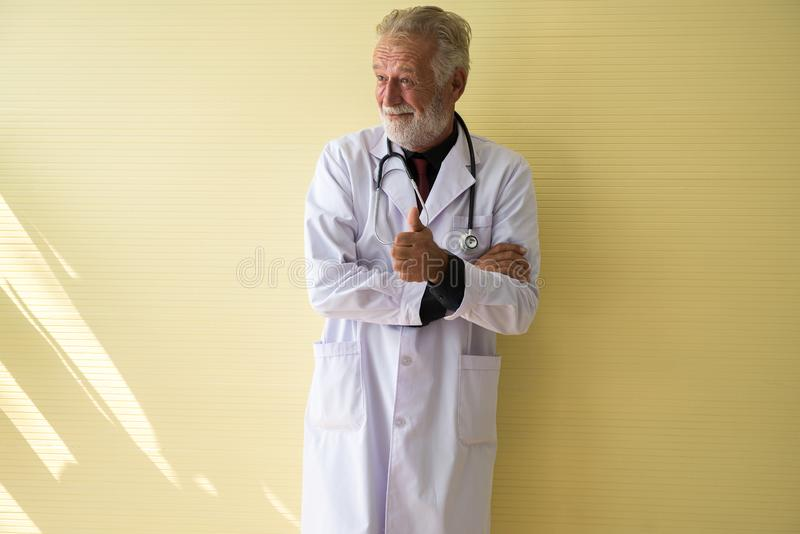 O retrato do doutor superior que levanta-se e que mostra o polegar na atitude de pensamento positiva do hospital, a feliz e do so fotografia de stock