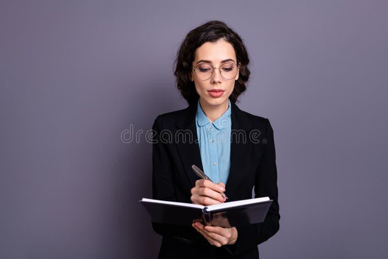 O retrato do editor focalizado encantador bonito do ensaio do diário da mão da posse do freelancer da senhora quer o encontro de  fotografia de stock