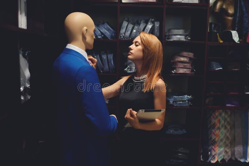 O retrato do empresário da jovem mulher endireita o laço no manequim ao estar com a almofada de toque em sua loja imagem de stock royalty free