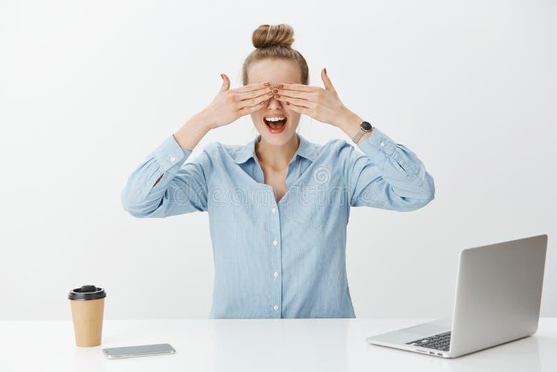 O retrato do empresário fêmea bonito surpreendido no escritório, cobrindo eyes com palmas e espera impacientemente por fotografia de stock royalty free