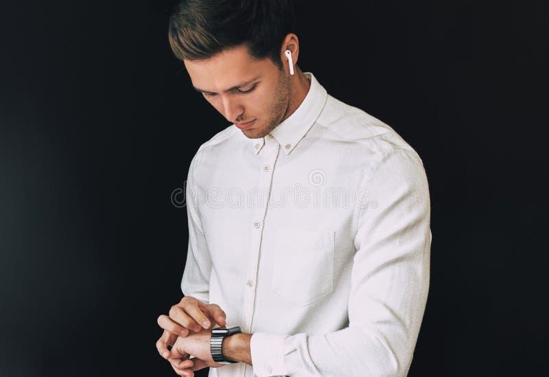 O retrato do estúdio da camisa branca vestindo esperta do homem novo, olhando o smartwatch que levanta sobre o fundo preto apress imagens de stock