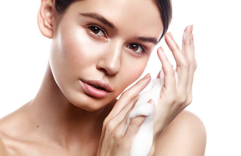 O retrato do estúdio da mulher bonita limpa a pele com a espuma no whit imagens de stock