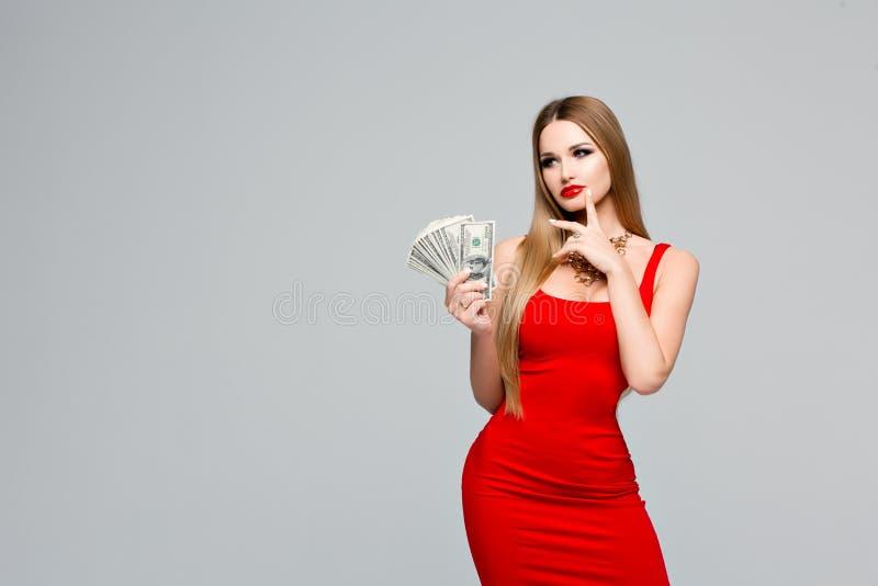 O retrato do estúdio da mulher bonita no vestido vermelho guarda o dinheiro, pensa onde gastá-lo Menina delgada nova com fotos de stock royalty free