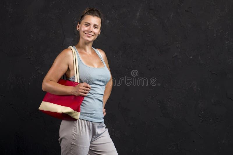 O retrato do estúdio de um jovem ostenta a menina com uma bolsa em seu ombro A mulher na juventude elegante veste-se imagens de stock royalty free