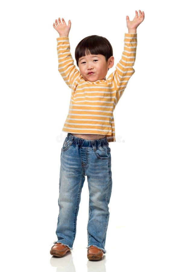 O retrato do estúdio de uma criança masculina asiática do leste com ambas as mãos abre imagem de stock royalty free