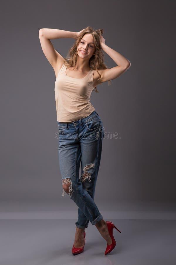 O retrato do estúdio do modelo bonito da mulher com os pés longos do corpo surpreendente que inclinam agains mura calças de brim  imagem de stock