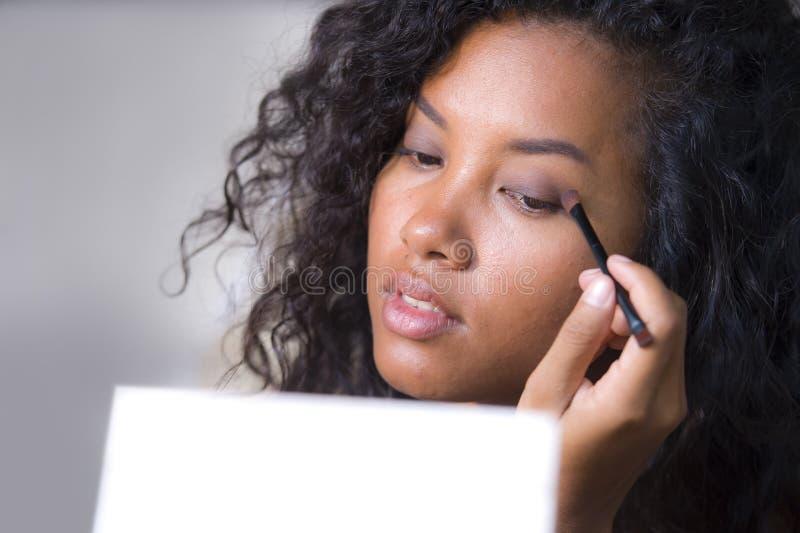 O retrato do estilo de vida da mulher latino-americano feliz e bonita nova que aplica a cara compõe usando a escova na pálpebra q fotografia de stock