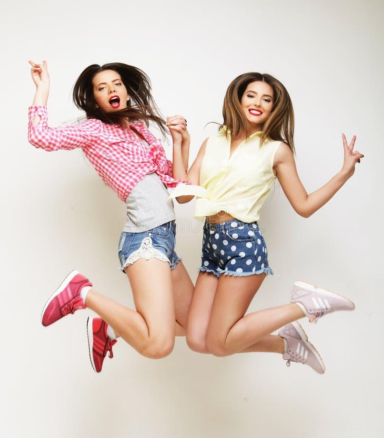 O retrato do estilo de vida de dois melhores amigos novos das meninas do moderno salta fotos de stock royalty free