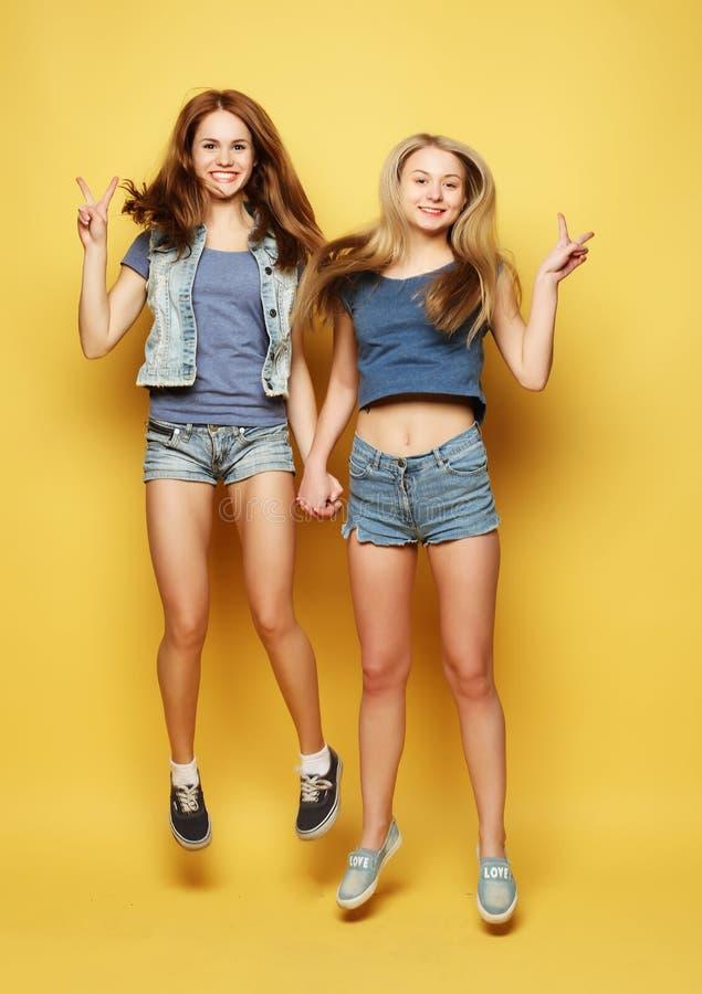 O retrato do estilo de vida de dois melhores amigos das moças salta sobre o YE imagens de stock