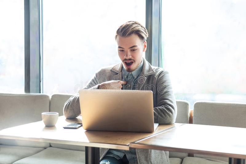 O retrato do freelancer novo farpado inacreditável feliz no blazer cinzento está sentando-se apenas no café e está tendo-se a pro imagens de stock royalty free