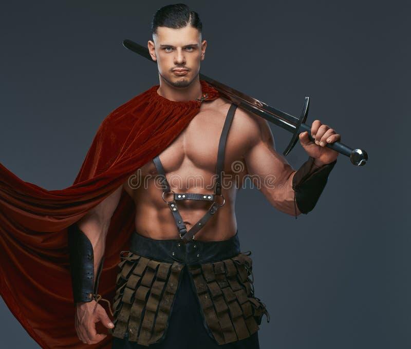 O retrato do guerreiro de Grécia antigo com um corpo muscular vestiu-se em uniformes da batalha guarda a espada em seu ombro fotografia de stock