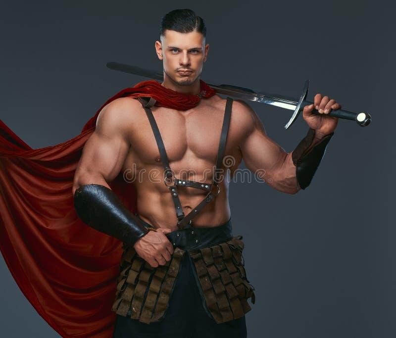 O retrato do guerreiro de Grécia antigo com um corpo muscular vestiu-se em uniformes da batalha guarda a espada em seu ombro imagem de stock royalty free