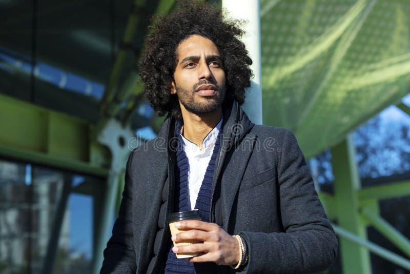 O retrato do homem afro considerável alegre no vestuário desportivo que levanta para guardar farpado do homem novo da câmera leva foto de stock