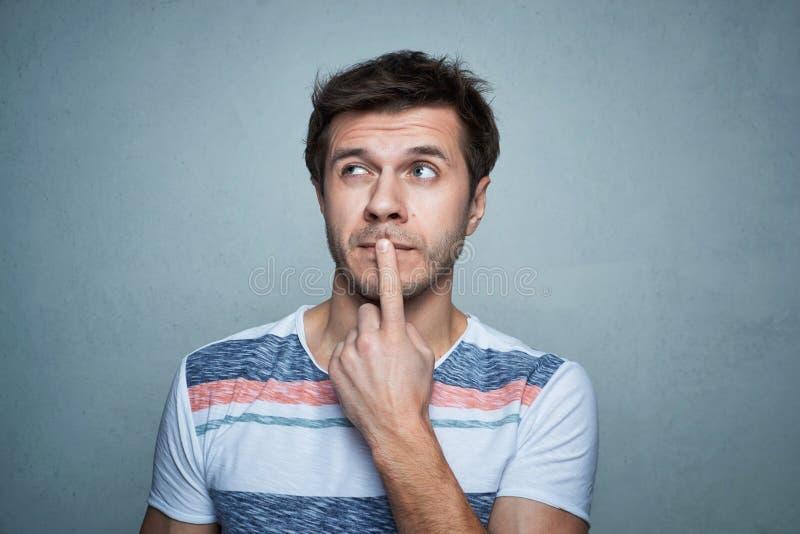 O retrato do homem caucasiano com pensa a emoção em um fundo cinzento fotografia de stock royalty free