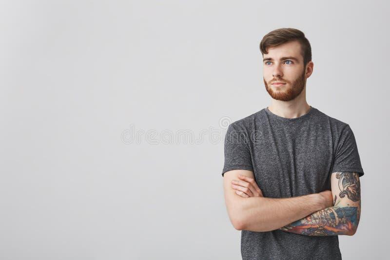 O retrato do homem caucasiano maduro seguro com barba e da tatuagem disponível que guarda as mãos cruzou-se, olhando de lado com imagem de stock royalty free