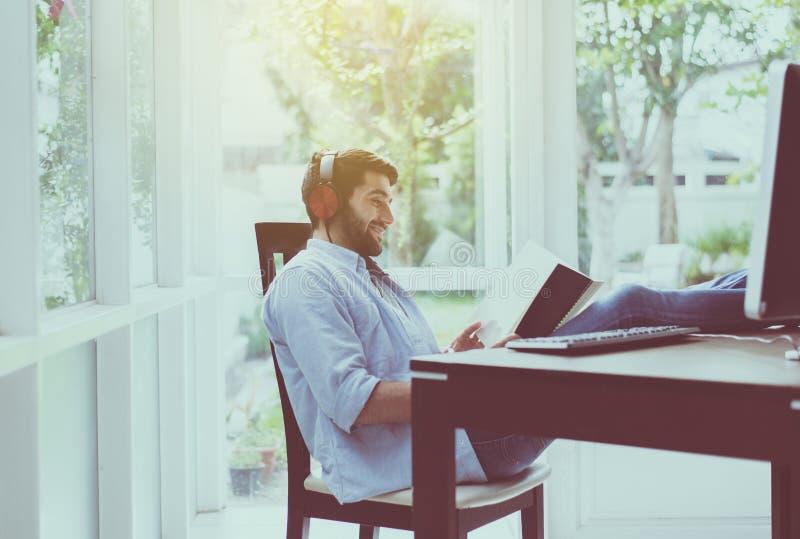 O retrato do homem considerável com o livro de leitura da barba e a escuta a música em linha no espaço coworking, feliz e o sorri fotos de stock royalty free