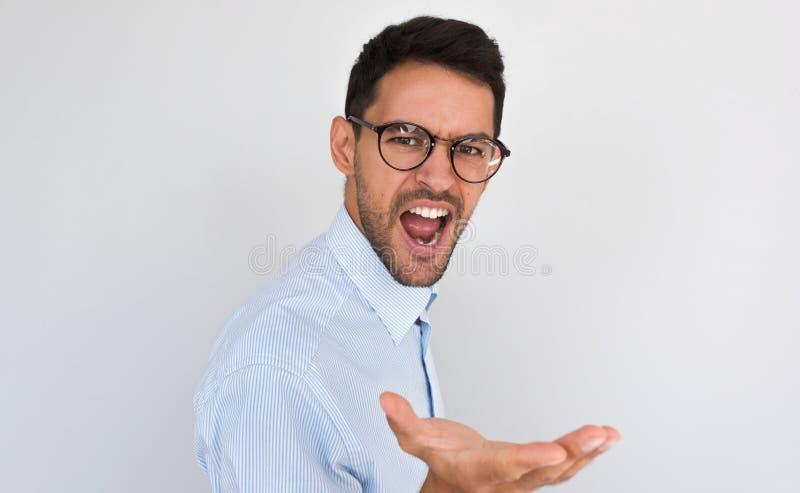 O retrato do homem considerável novo irritado exclama, sente furioso ao falar com alguém, levantando no fundo branco do estúdio imagens de stock