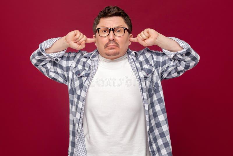 O retrato do homem de negócio envelhecido médio sério na camisa quadriculado ocasional, posição dos monóculos, pondo os dedos nas fotos de stock