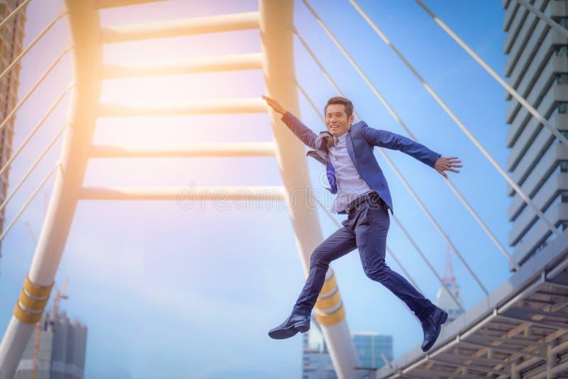 O retrato do homem de negócio que salta com braços comemora acima no blurr fotos de stock