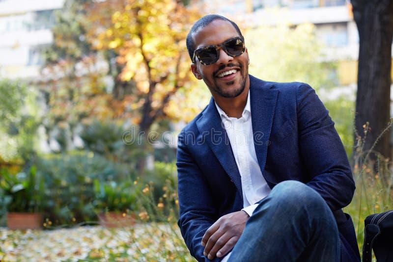O retrato do homem de negócios afro-americano novo seguro feliz no vestuário formal e os óculos de sol que sentam-se na cidade es foto de stock