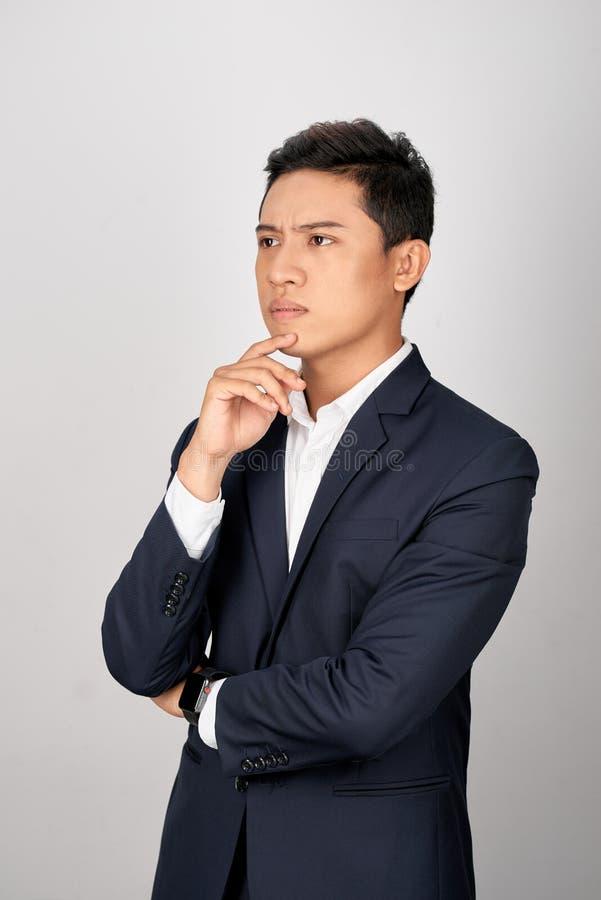O retrato do homem de negócios asiático novo atrativo está confundindo sobre o fundo branco fotos de stock royalty free