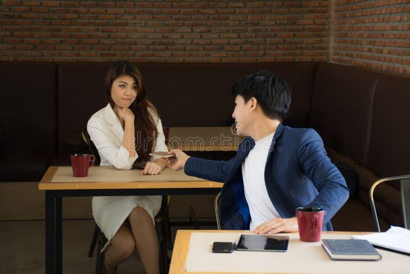 O retrato do homem de negócios atrativo que guarda o telefone celular em sua mão dá-à uma menina bonita fotografia de stock