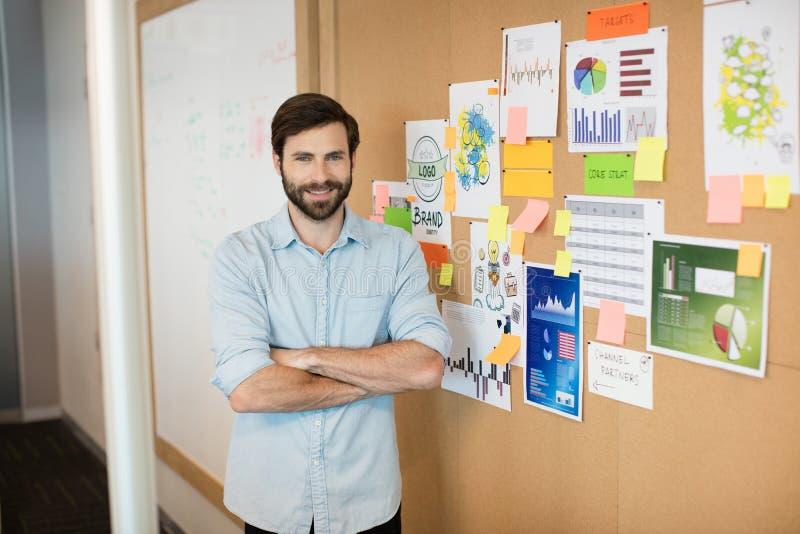 O retrato do homem de negócios de sorriso novo com braços cruzou-se pela placa macia no escritório imagem de stock royalty free