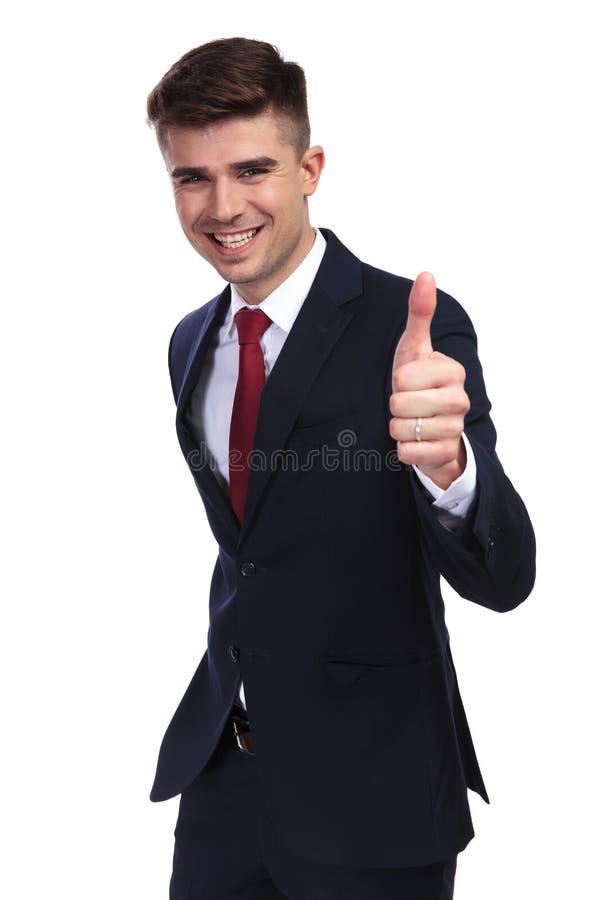 O retrato do homem de negócios de riso que faz os polegares levanta o sinal fotografia de stock royalty free