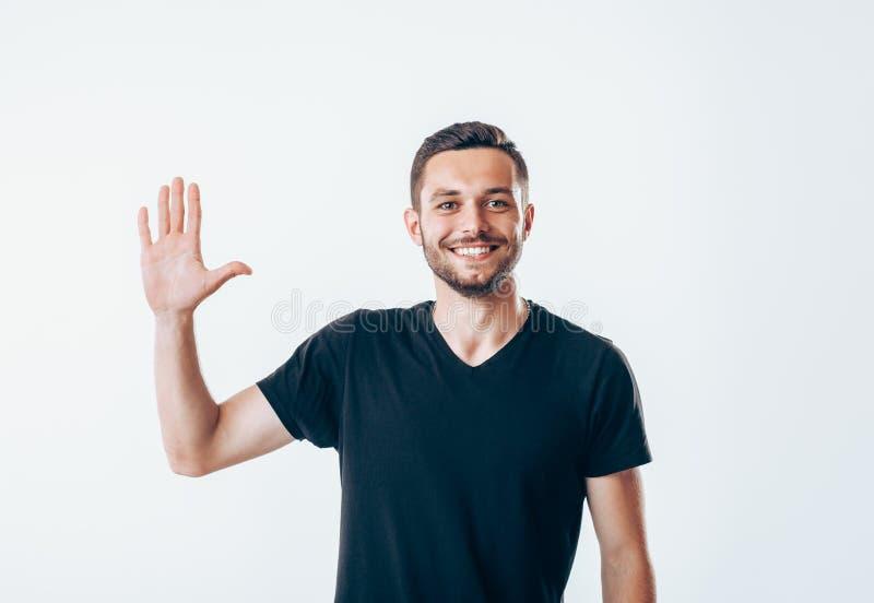 O retrato do homem de sorriso com mão aumentou no cumprimento foto de stock royalty free