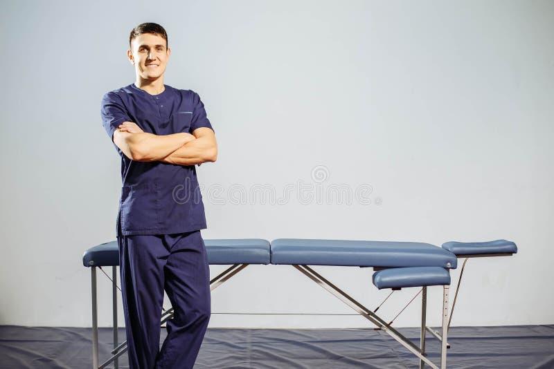 O retrato do homem de sorriso novo no uniforme perto da massagem deita imagens de stock royalty free