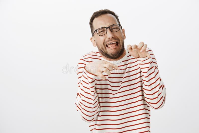 O retrato do homem emotivo engraçado nos vidros que fazem as caras e que imitam as patas do dinossauro com cede a caixa, gritando imagem de stock royalty free