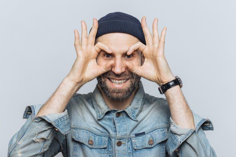 O retrato do homem farpado hppy faz o eyewear com dedos, tem o st imagem de stock