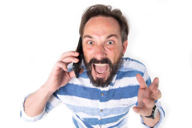 O retrato do homem farpado maduro furioso vestiu-se na camisa com linhas azuis grita sobre telefone celular isolado no fundo bran fotografia de stock royalty free