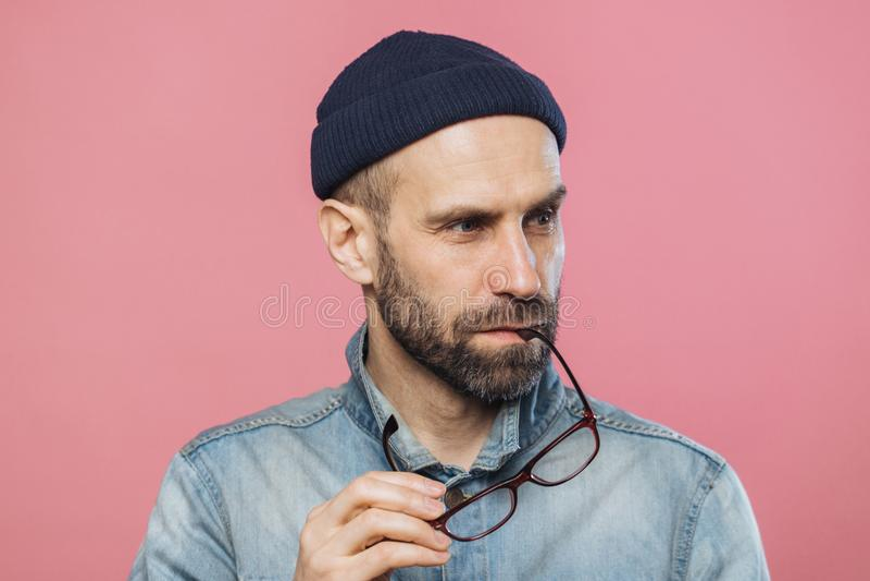 O retrato do homem farpado pensativo decola vidros, veste o revestimento à moda da sarja de Nimes e o chapéu, isolados sobre o fu imagens de stock royalty free