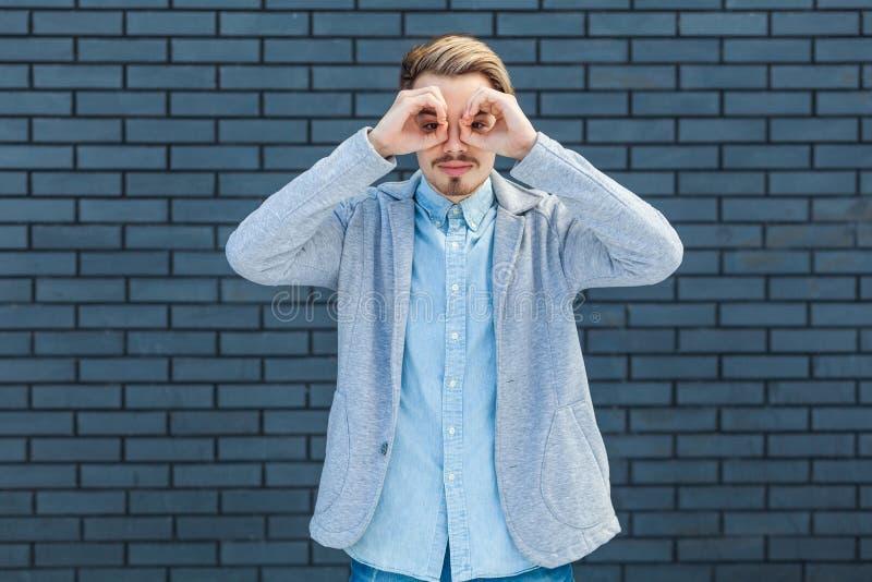 O retrato do homem louro novo considerável atento sério na posição do estilo ocasional com binóculos gesticula a mão nos olhos e  foto de stock royalty free