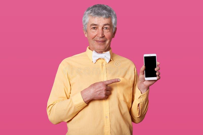 O retrato do homem maduro atrativo com cabelo e os enrugamentos cinzentos, vestiu a camisa amarela em um tom e no laço branco, gu imagem de stock royalty free